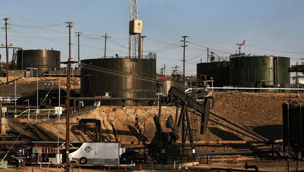This Thursday March 6, 2014 photo shows pumpjacks operating in front of a hydraulic fracturing site in the Inglewood oil fields in the Baldwin Hills area of Los Angeles - Sputnik International