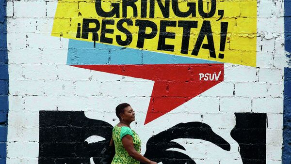 A woman walks past graffiti which reads Gringo, respect us! in Caracas March 10, 2015. President Nicolas Maduro was seeking special decree powers from Venezuela's parliament on Tuesday in response to new U.S. sanctions, drawing opposition protests of a power-grab - Sputnik International