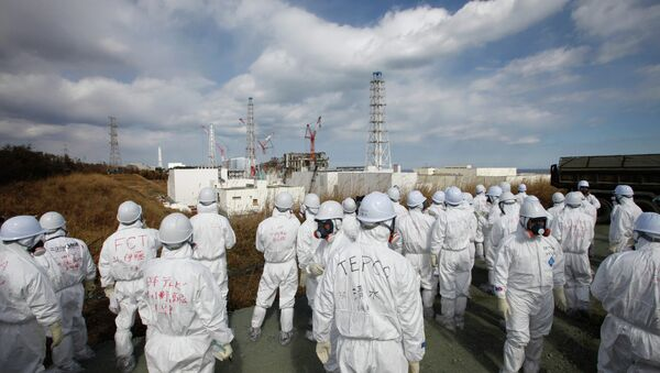 Members of the media wearing protective suits and masks report as they are escorted by TEPCO employees at Tokyo Electric Power Co. (TEPCO)'s tsunami-crippled Fukushima Daiichi nuclear power plant in Okuma, Fukushima prefecture on February 20, 2012 - Sputnik International