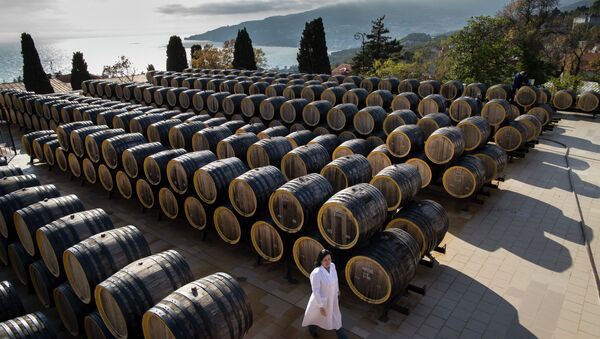 In this photo taken on Tuesday, Oct. 28, 2014, Rameta Kushkhova walks by barrels of wine in the state-owned Massandra winery in Yalta, Crimea - Sputnik International