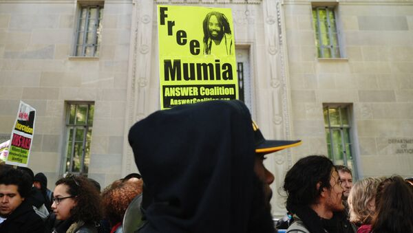 Protestors stand before an image of Mumia Abu-Jamal outside the US Department of Justice on April 24, 2012 in Washington - Sputnik International