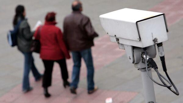 A police CCTV camera observes people walking in the Embankment area of central London - Sputnik International