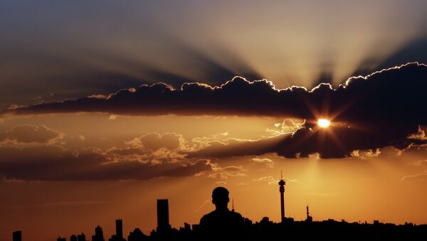 A man watches the sun set in as he overlooks the skyline in Johannesburg, South Africa - Sputnik International