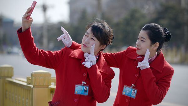 Chinese hostesses use a mobile phone to take a photo during the third session of the 12th National People's Congress outside the Great Hall of the People in Beijing - Sputnik International