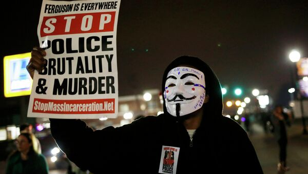 A protestor wearing a Guy Fawkes mask holds a sign as demonstrators march through the streets of Ferguson, Missouri, March 12, 2015 - Sputnik International