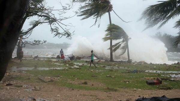 In this image provided by UNICEF Pacific people walk along the shore where debris is scattered in Port Vila, Vanuatu, Saturday, March 14, 2015, in the aftermath of Cyclone Pam - Sputnik International