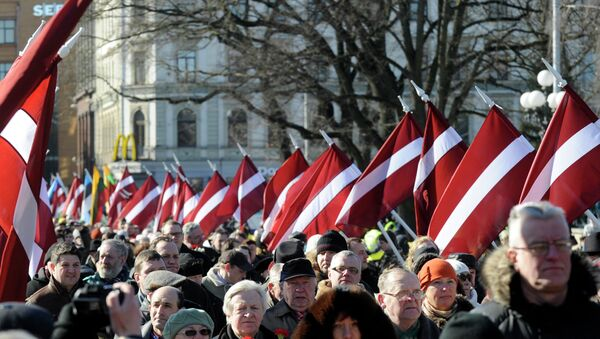 People carry Latvian flags at the march in Riga, Latvia - Sputnik International