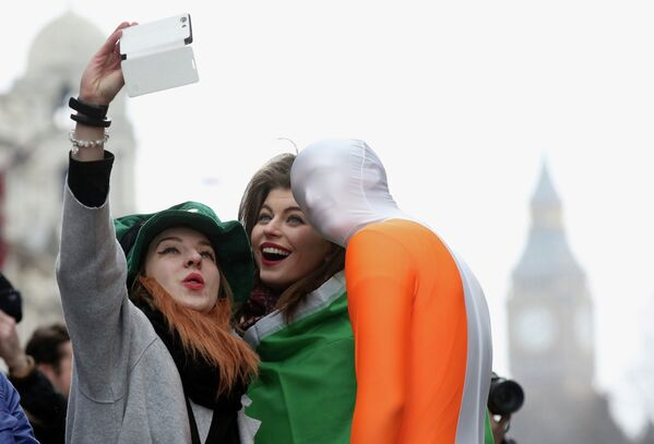 Young women from Moscow have their picture taken with a participant of the St Patrick's Day parade, central London. - Sputnik International