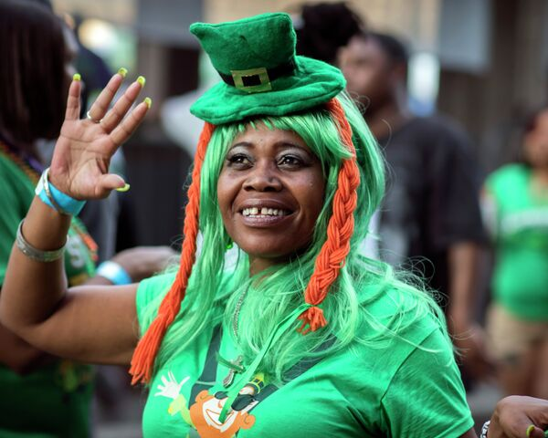 A woman dressed as a leprechaun waves to friends as she walking along River Street during the start of a four-day St. Patrick's Day celebration on River Street in Savannah, Georgia. - Sputnik International