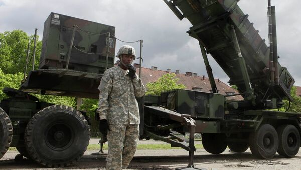 A US soldier stands next to a Patriot surface-to-air missile battery at an army base in Morag, Poland - Sputnik International