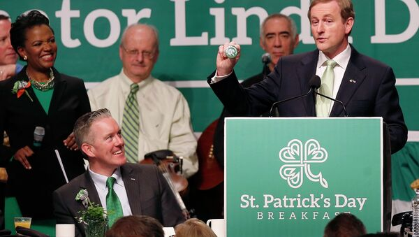 Prime Minister Enda Kenny of Ireland, right, holds a badge while speaking at the annual St. Patrick's Day Breakfast in Boston, as host state Sen. Linda Dorcena Forry, left, looks on, March 16, 2014. - Sputnik International