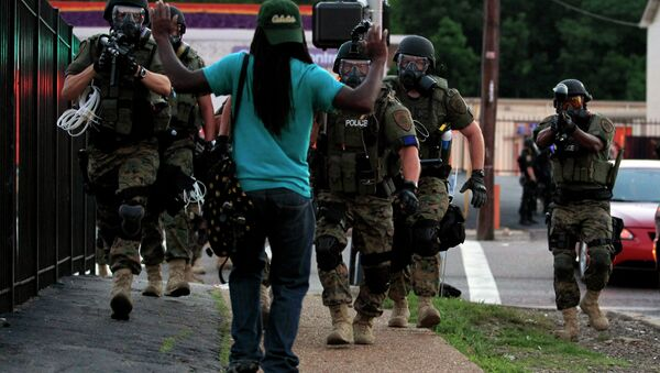 In this Aug. 11, 2014, file photo, police wearing riot gear walk toward a man with his hands raised Monday, Aug. 11, 2014, in Ferguson - Sputnik International