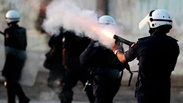 Riot police fire tear gas as they chase Bahraini anti-government protesters throwing stones and petrol bombs on the outskirts of the capital of Manama, Bahrain - Sputnik International