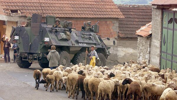 A German armoured vehicle part of the NATO-led KFOR troops drives past a herd of sheep 17 June 1999 in Orahovac, south western Kosovo. - Sputnik International