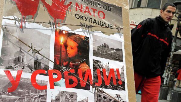 """A man walks past a poster with the reading """"Ten years of NATO occupation of Serbia"""", and displaying images from 1999 NATO air campaign against Serbia and Montenegro, in Belgrade on March 23, 2009. - Sputnik International"""