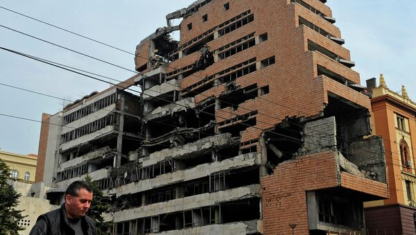 A man walks past the building of former federal military headquarters in Belgrade on March 24, 2010, destroyed during the 1999 NATO air campaign against Yugoslavia. - Sputnik International