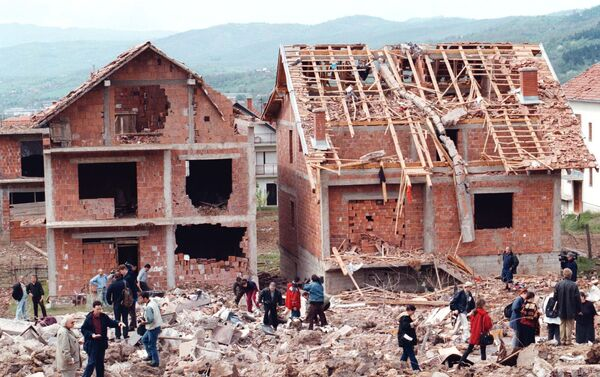 Serb civilians and reporters walk around a residential area damaged during a NATO attack on a neighboring army compound (300 kilometers south of Belgrade), Wednesday, April 28, 1999. - Sputnik International
