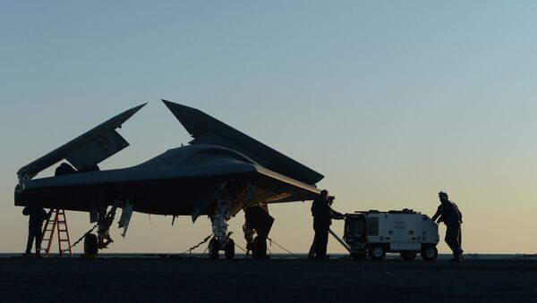 Sailors working on an X-47B Unmanned Combat Air System (UCAS) at dawn aboard the aircraft carrier USS George H.W. Bush - Sputnik International