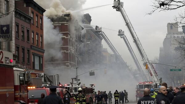 New York City Fire Department and Police stand by as firefighters fight a fire near where a residential apartment building collapsed and was engulfed in flames in New York City's East Village neighborhood - Sputnik International