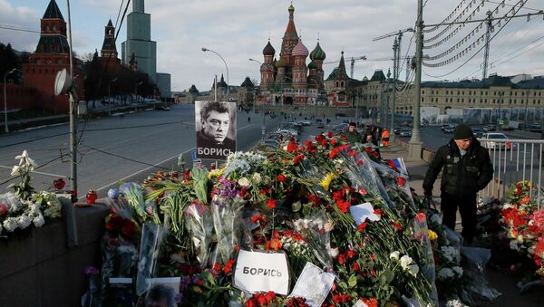 A man walks past flowers at the site where Kremlin critic Boris Nemtsov was murdered on February 27, at the Great Moskvoretsky Bridge, with St. Basil's Cathedral seen in the background, in central Moscow March 6, 2015 - Sputnik International