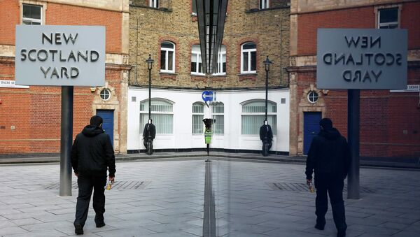 A man walks past the rotating triangular sign outside New Scotland Yard in central London March 17, 2015 - Sputnik International