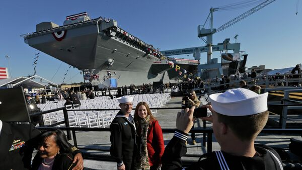People pose for photos in front of Navy aircraft carrier USS Gerald R. Ford during the christening of the ship in November 2013. - Sputnik International