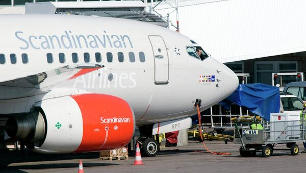 The pilot of an SAS Boeing 737 series jets speaks to his ground staff through the cockpit window at the gate of Terminal 4 on Arlanda airport in Stockholm, Sweden, Tuesday April 29, 2008. The Scandinavian Airline Group on Tuesday posted a first-quarter net loss of 1.08 billion kronor (US$181 million, euro116 million), citing higher fuel costs and growing competition and said it would slash 1,000 jobs to reduce costs. File photo - Sputnik International