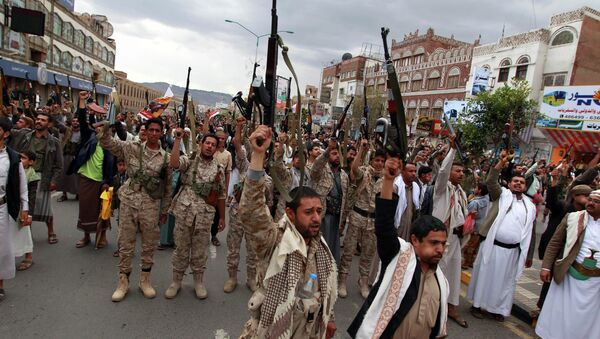 Shiite rebels, known as Houthis, hold up their weapons to protest against Saudi-led airstrikes, as they chant slogans during a rally in Sanaa, Yemen, Thursday, March 26, 2015 - Sputnik International