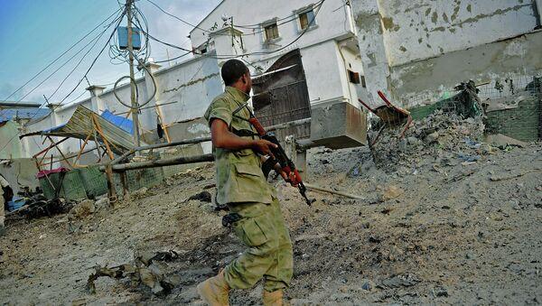 A solder walks past at the scene of a car bomb attack and armed raid by Al Shebab militants on the Maka al Mukarama hotel in Mogadishu - Sputnik International