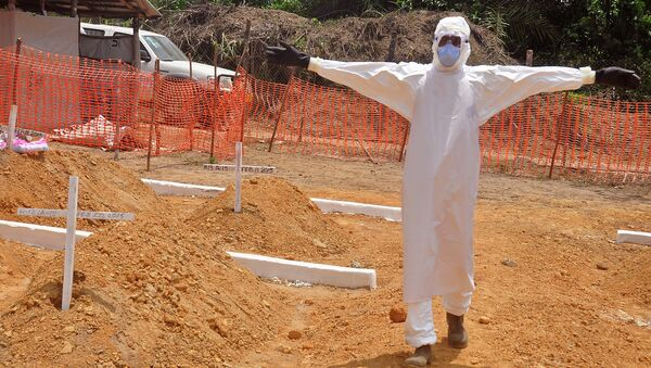 A health worker holds up his arms after he and others buried a person that they suspect died form the Ebola virus at a new graveyard on the outskirts of Monrovia, Liberia - Sputnik International
