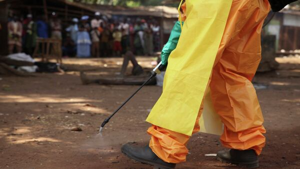 A member of the French Red Cross disinfects the area around a motionless person suspected of carrying the Ebola virus as a crowd gathers in Forecariah, Guinea - Sputnik International