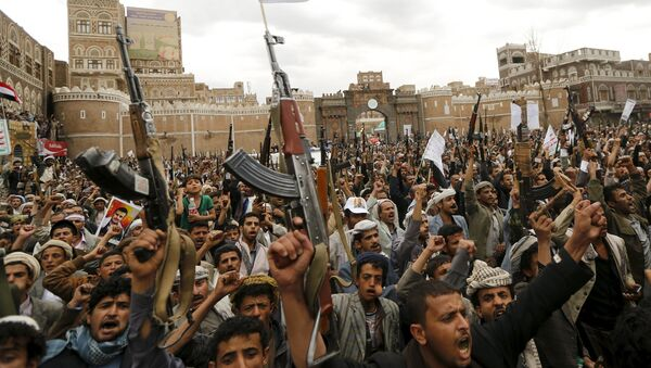 Shi'ite Muslim rebels hold up their weapons during a rally against air strikes in Sanaa - Sputnik International