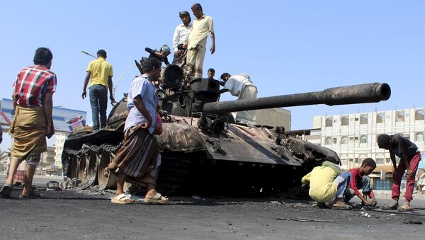 People gather near a tank burnt during clashes on a street in Yemen's southern port city of Aden March 29, 2015 - Sputnik International