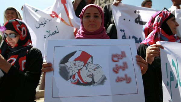 A Yemeni woman holds a poster during a rally against Saudi-led coalition airstrikes against Huthi rebels on March 29, 2015 in Sanaa - Sputnik International