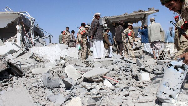 Soldiers and Houthi fighters inspect the damage caused by air strikes on the airport of Yemen's northwestern city of Saada, a Houthi stronghold near the Saudi border, March 30, 2015 - Sputnik International