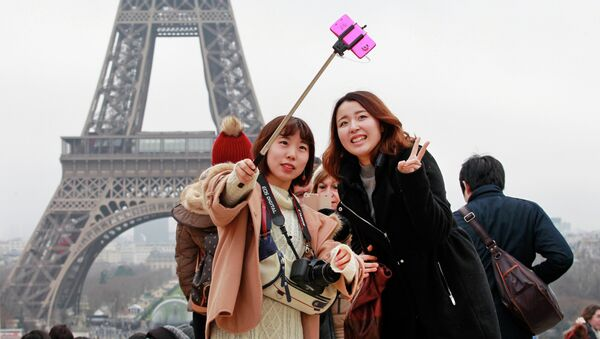 Tourists use a selfie stick on the Trocadero Square, with the Eiffel Tower in background, in Paris - Sputnik International