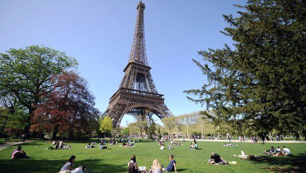 People enjoy the sunny spring weather near the Eiffel tower in Paris - Sputnik International