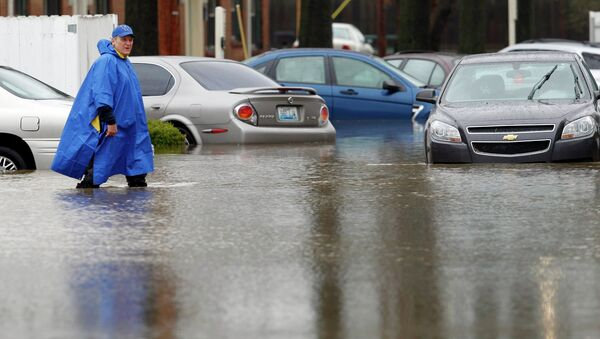 A resident of the Guardian Court Apartments wades through high water after heavy rains caused flash flooding and forced some to leave their homes in Louisville, Kentucky - Sputnik International