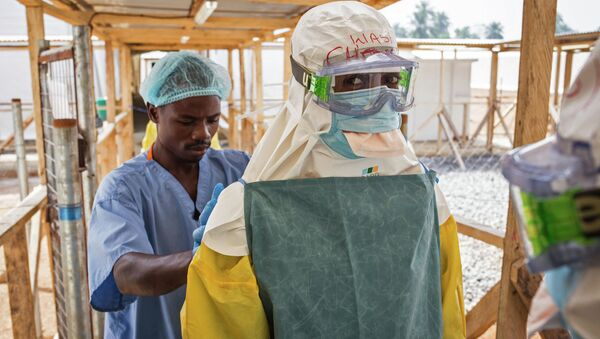 In this photo taken on Monday, March 2, 2015, a health care worker prepares a colleague's virus protective gear before entering a high risk zone at an Ebola virus clinic operated by the International Medical Corps in Makeni, Sierra Leone - Sputnik International