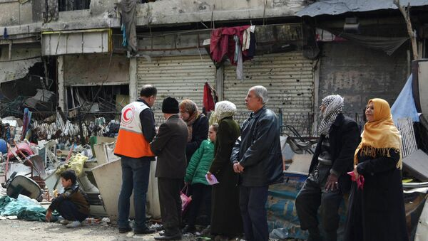 Residents wait to receive humanitarian aid at the Palestinian refugee camp of Yarmouk, in Damascus March 11, 2015 - Sputnik International