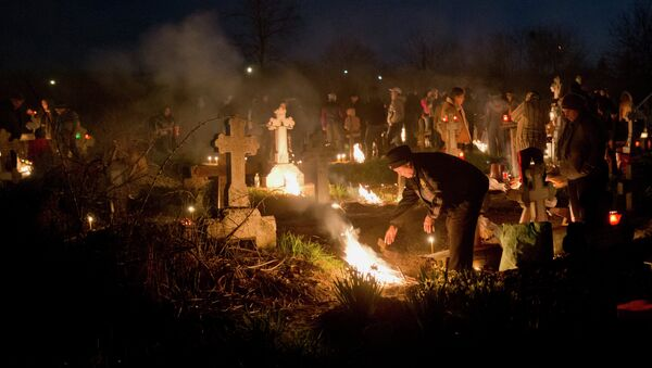 People stand by fires they lit by a relative's grave in a cemetery during an Orthodox Palm Sunday memorial for the departed in Herasti, southern Romania, early Sunday, April 5, 2015 - Sputnik International
