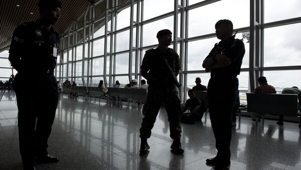 A member of the Malaysian Army (C) and a Malaysian policemen are silhouetted as they stand guard at Kuala Lumpur International Airport (KLIA) in Sepang, outside Kuala Lumpur on March 16, 2014 - Sputnik International