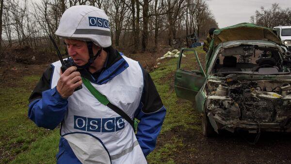 OSCE observers inspect a damaged car near Shyrokyne village, eastern Ukraine, Monday, March 30, 2015 - Sputnik International