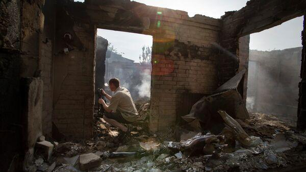 A journalist films a destroyed house following a mortar attack in Semyonovka village, outside Slavyansk, Ukraine, Friday, May 23, 2014 - Sputnik International