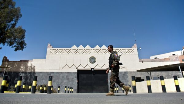 A Houthi fighter wearing an army uniform, walks past the gate of the main entrance of the US embassy after Yemeni police opened the road in front of it in Sanaa, Yemen, Wednesday, March 4, 2015 - Sputnik International