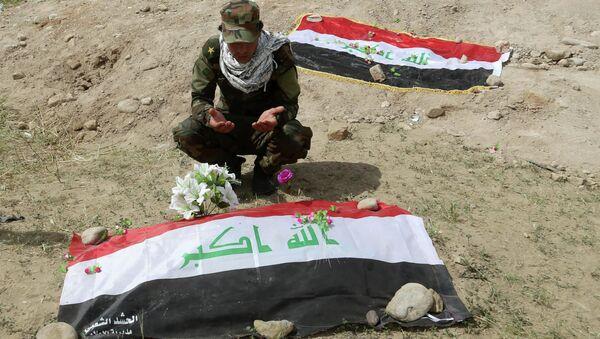 Shiite militiaman prays at a mass grave - Sputnik International