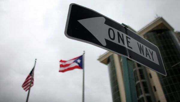 In this May 4, 2012 photo, the flags of Puerto Rico and the U.S. wave behind an English one-way traffic sign in Guaynabo, Puerto Rico, one of only a few places in Puerto Rico with street signs in English - Sputnik International