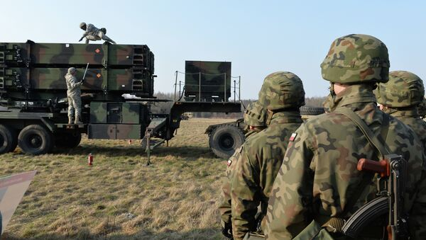 Polish soldiers watch as US troops from the 5th Battalion of the 7th Air Defense Regiment emplace a launching station of the Patriot air and missile defence system at a test range in Sochaczew, Poland, on March 21, 2015 - Sputnik International