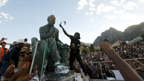 A student beats the statue of Cecil John Rhodes with a belt as it is removed from the University of Cape Town (UCT), April 9, 2015 - Sputnik International