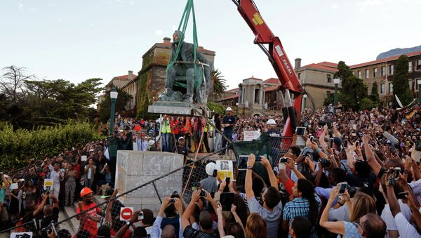 Cheering students surround the decades old bronze statue of British colonialist Cecil John Rhodes, as it is removed from the campus at the Cape Town University, Cape Town, South Africa, Thursday, April 9, 2015 - Sputnik International